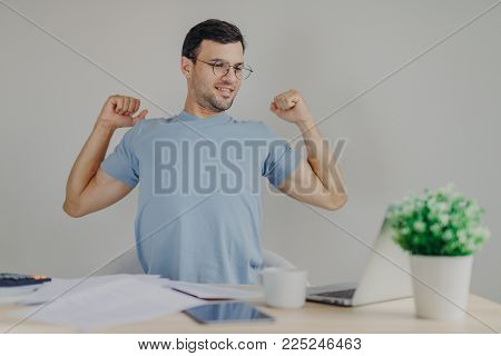 Overworked male freelancer stretches at work place, just finishes with work, looks happily into screen of portable laptop, satisfied with results , isolated over grey background. People and finances