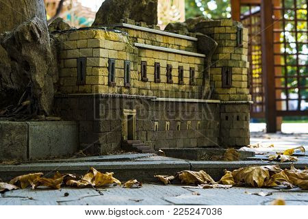 Sculpture or model of the building made of metal. Garden decorative building. Architectural composition of stone figures of the animal kingdom and miniature buildings in the form of a tower of idols.