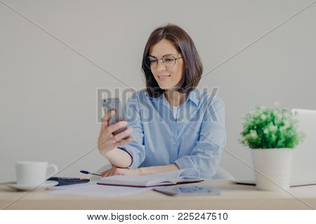Successful brunette female freelancer recieves good news on smart phone while works on laptop computer, reads post on website, makes notes in diary, drinks strong coffee, makes some calculations