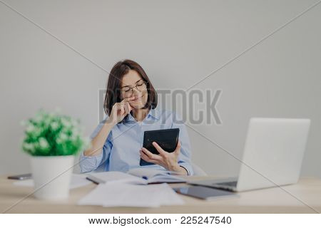 Cheerful female financial manager holds calculator in hands, being satisfied with recieved figures, makes report on laptop computer, analyzes company`s net profit. People and finances concept