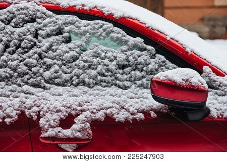 Red car covered with thick snow. Winter blizzard and bad weather conditions. Parked car covered with snow. Transportation and winter concept.