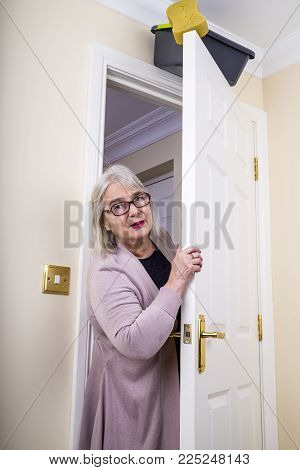 April Fool's Day Trick. Lady walking into a room, with a bucket of water and sponge about to fall on to her.  April Fool's Day joke.