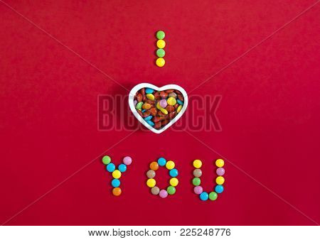 on a red background written with candies I love you a bowl of a plate a sweet candy in the shape of a heart with colorful round candies