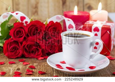 Cup with coffee in front of bouquet of red roses and candles on wooden background. Valentines day concept. Happy Mother's day concept. Focus on cup of coffee.