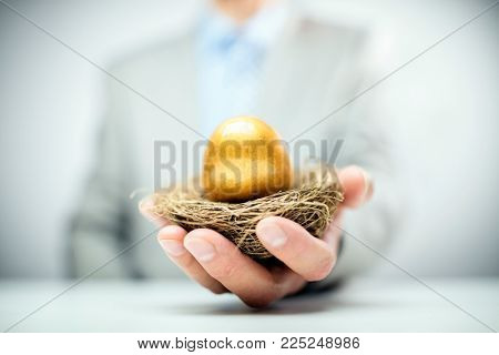 Retirement savings golden nest egg in a businessmans hand