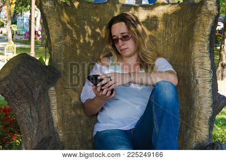 The girl in the decorative chair. Elegant armchair in the trunk of a tree. Original painting. The girl in glasses sits carved chair and climbs into the smartphone. A woman is sitting on a carved wooden throne using a tablet.