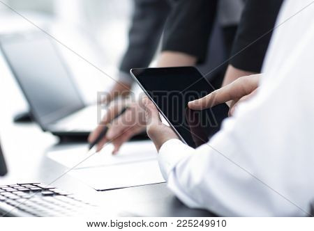 closeup.employees working with a tablet computer and a laptop.