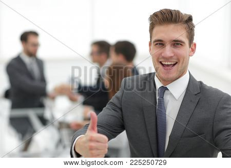 Portrait of happy energetic businessman with thumbs up while  co