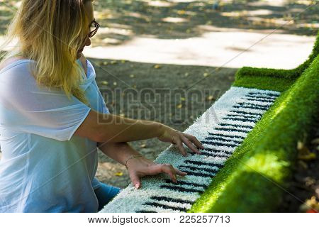 The girl at the piano. The tool is covered with a decorative cloth. Simulation of the game on the instrument. A woman in glasses plays the decorative piano.