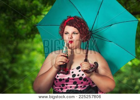 Girl Sheltering From sun Beneath Umbrella and drink