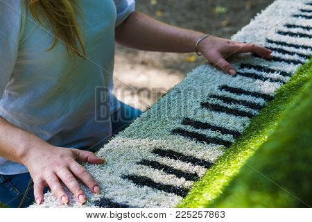 Girl behind a decorative piano. Hands on the keys. The keys are shown on the fabric. A woman in glasses plays the decorative piano.