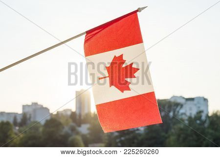 Flag of Canada from window on sunset background
