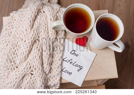 One long life of love is an abstract symbolic image. Couple of cups, background warm scarf, in home interior, napkin with text.