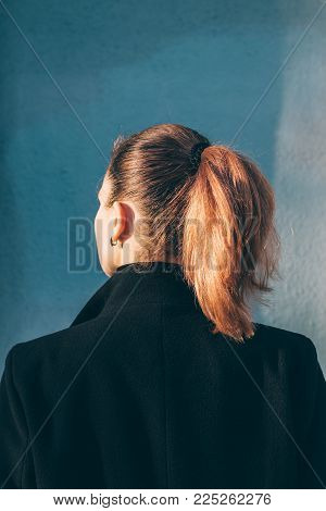 View From The Back Of A Beautiful Girl With Red Hair In A Coat In Sunlight, Vertical Cropping