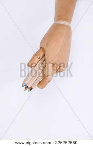 close-up view of dummy holding colorful pastels isolated on white