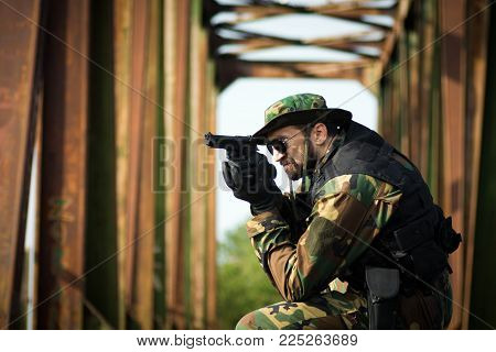 The army soldier in military uniform is aiming with pistol outdoors on old bridge.