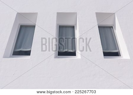 View on three windows with curtains of a white housee.
