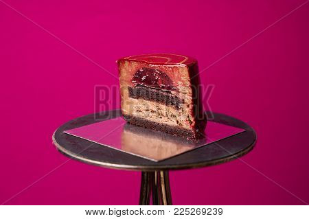 Glamor cake on pink background. The Glamor is made from a thin layer of chocolate biscuit, chocolate mousse, crimson jam. Mirror glaze covering the cake is made of natural Belgian chocolate.
