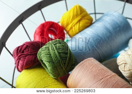 Metal basket with color sewing threads and crocheting clews on light background, closeup