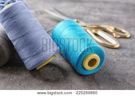 Colorful sewing threads on grey background, closeup