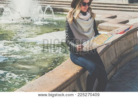 Young female tourist in hat and sunglasses is sitting on street of European city near fountain, holding destination map.Girl is traveler looking for way on map, looks at sights. Tourism, vacation, trip.