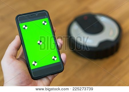 Man Using Mobile App To Control Robotic Vacuum Cleaner. Space For Your Text. Chroma Key.
