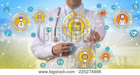 Unrecognizable male physician is tracking the pulse trace of a remote worker via smart watch. Healthcare concept for internet of medical things, IoMT, internet of things, IoT, wearable technology.