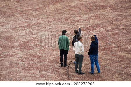 a group of four men looking ad discussing and talking while pointing towards the top with there hand on the new Lammermarkt square in Leiden, The Netherlands 29 September 2017