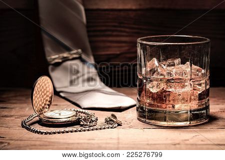 A conceptual image of aa glass of liquor, a pocket watch, and a neck tie.