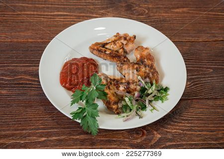Roasted chiken wings on a plate. Appetizing dish on the wooden brown table.