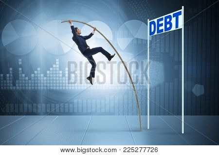 Businessman pole vaulting over debt in business concept