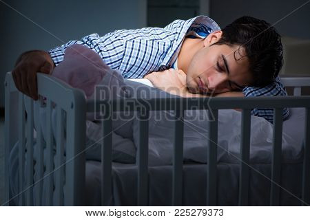 Young father dad sleeping while looking after newborn baby