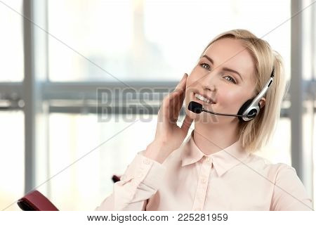 Face of beautiful smiling happy woman in headset. Portrait of smiling caucasian customer service and support blond woman wearing headset in bright office and nodding head.