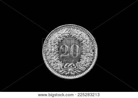 A Macro Image Of A Swiss 20 Centimes Coin Isolated On A Black Background