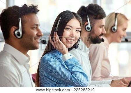 Young cheerful beautiful business woman in headset. Smiling female asian customer service representative looking at the camera.