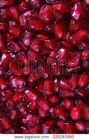 Pomegranate seeds red seed closeup pattern texture as background. Macro photo. Ruby color.