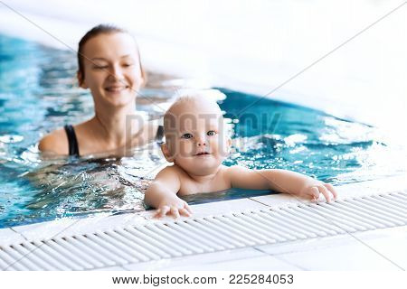 Mother Teaching Baby To Swim. Portrait Of A Charming 11 Months Child In The Classroom In A Swimming