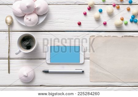 White smart phone on white wood with coffee and cookies. Top view with Clipping path.