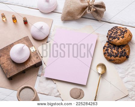 Blank cardboard tag next to sweets on white wooden table