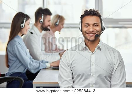 Young friendly male customer service operator. Portrait of a smiling businessman with headsets in a call centre. Bright windows background.