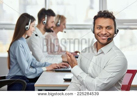 Call center operator pointing at his colleagues. Indian handsome young man pointing at his coworkers. They are working.