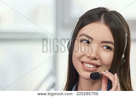 Friendly receptionist smiling and wearing a headset. Young asian woman wearing telephone headset ready to take your call.