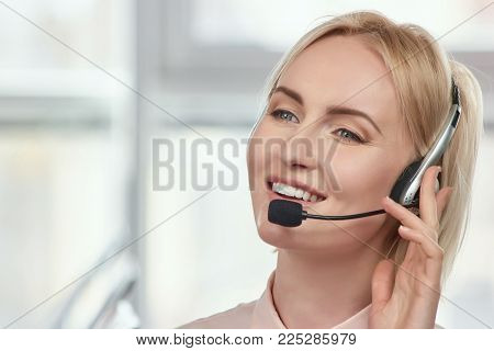 Mature operator with headset portrait. Closeup of successful mature blond woman who is wearing headset.