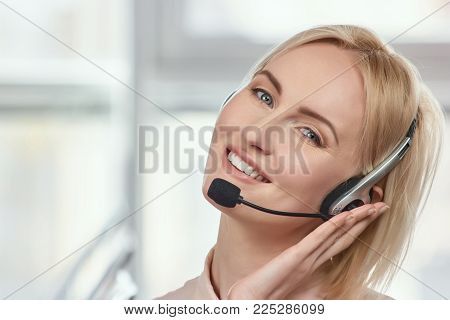 Mature blond woman holding headset. Portrait of attractive blonde call centre operator in a headset with nodded head.