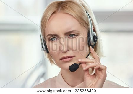 Portrait of sad call center operator. Blond mature woman with frown face dissapoint with something.