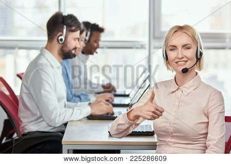 Blond lady operator giving thumb up. Mature woman with blond hair and headset shows thumb up in front of working co-workers backgorund.