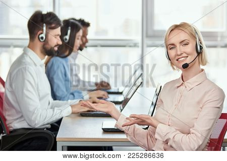 Female operator recommeding her co-workers. Lady with headset in call center office pointing at her colleagues using both hands.