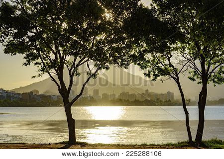 Late summer afternoon with the sun shining on the water and through the trees of the Rodrigo de Freitas lagoon in Rio de Janeiro with its buildings and mountains in the background