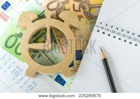 Time for invest, tax and debt calculation, pencil on white notepad paper with wooden alarm clock on Euro money and salary slip.
