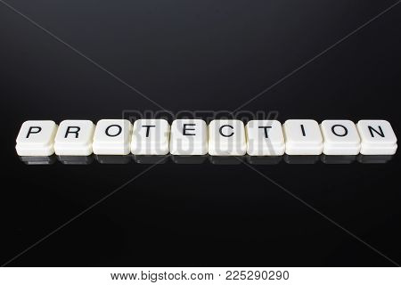 Protection text word title caption label cover backdrop background. Alphabet letter toy blocks on black reflective background. White alphabetical letters..